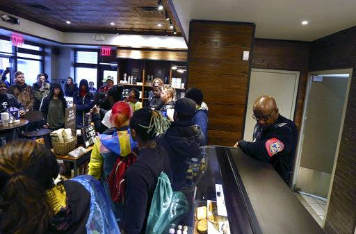 A plain-clothed police officer, right, mans a position behind the counter at the Starbucks that has become the center of protests Monday, April 16, 2018, in Philadelphia. The CEO of Starbucks arrived in Philadelphia hoping to meet with two black men who were arrested when the coffee chain's employees called 911 and said they were trespassing. Meanwhile, protesters took over the shop Monday.