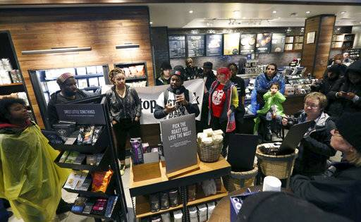 Demonstrators occupy the Starbucks that has become the center of protests Monday, April 16, 2018, in Philadelphia. The CEO of Starbucks arrived in Philadelphia hoping to meet with two black men who were arrested when the coffee chain's employees called 911 and said they were trespassing. Meanwhile, protesters took over the shop Monday.