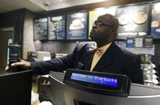 A plain-clothed police officer mans a position behind the counter at the Starbucks that has become the center of protests in Monday, April 16, 2018, in Philadelphia. The CEO of Starbucks arrived in Philadelphia hoping to meet with two black men who were arrested when the coffee chain's employees called 911 and said they were trespassing. Meanwhile, protesters took over the shop Monday.