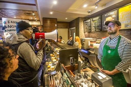 Local Black Lives Matter activist Asa Khalif, left, stands inside a Starbucks, Sunday April 15, 2018, demanding the firing of the manager who called police resulting the arrest of two black men on Thursday. The arrests were captured on video that quickly gained traction on social media. (Mark Bryant/The Philadelphia Inquirer via AP)