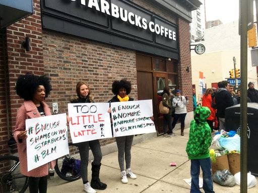 "Protesters gather outside a Starbucks in Philadelphia, Sunday, April 15, 2018, where two black men were arrested Thursday after Starbucks employees called police to say the men were trespassing. The arrest prompted accusations of racism on social media. Starbucks CEO Kevin Johnson posted a lengthy statement Saturday night, calling the situation ""disheartening"" and that it led to a ""reprehensible"" outcome."