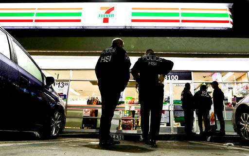 FILE - In this Jan. 10, 2018, file photo, U.S. Immigration and Customs Enforcement agents serve an employment audit notice at a 7-Eleven convenience store in Los Angeles. More local governments in California are resisting the state's efforts to resist the Trump administration's immigration crackdown, and political experts see politics at play as Republicans try to fire up voters in a state where the GOP has grown weak. Leaders in the Orange County city of Los Alamitos are scheduled to vote Monday, April 15, on a proposal for a local law to exempt the community from the state law.