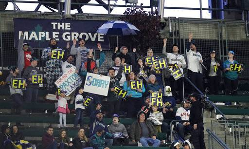 "Fans in the ""Maple Grove"" cheering section for Seattle Mariners starting pitcher James Paxton, of Canada, cheer and hold ""Eh"" signs as Paxton throws against the Houston Astros during the third inning of a baseball game, Monday, April 16, 2018, in Seattle."