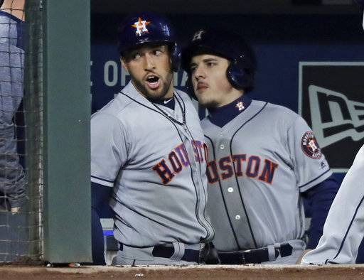 Houston Astros' George Springer, left, reacts in the dugout after he hit a solo home run against the Seattle Mariners in the first inning of a baseball game, Monday, April 16, 2018, in Seattle.