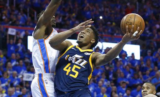 Utah Jazz guard Donovan Mitchell (45) shoots as Oklahoma City Thunder forward Jerami Grant, left, defends in the second half of Game 1 of an NBA basketball first-round playoff series in Oklahoma City, Sunday, April 15, 2018.