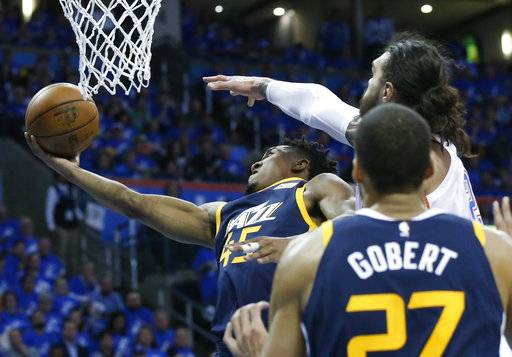 Utah Jazz guard Donovan Mitchell (45) shoots as Oklahoma City Thunder center Steven Adams, right, defends from behind in the second half of Game 1 of an NBA basketball first-round playoff series in Oklahoma City, Sunday, April 15, 2018.