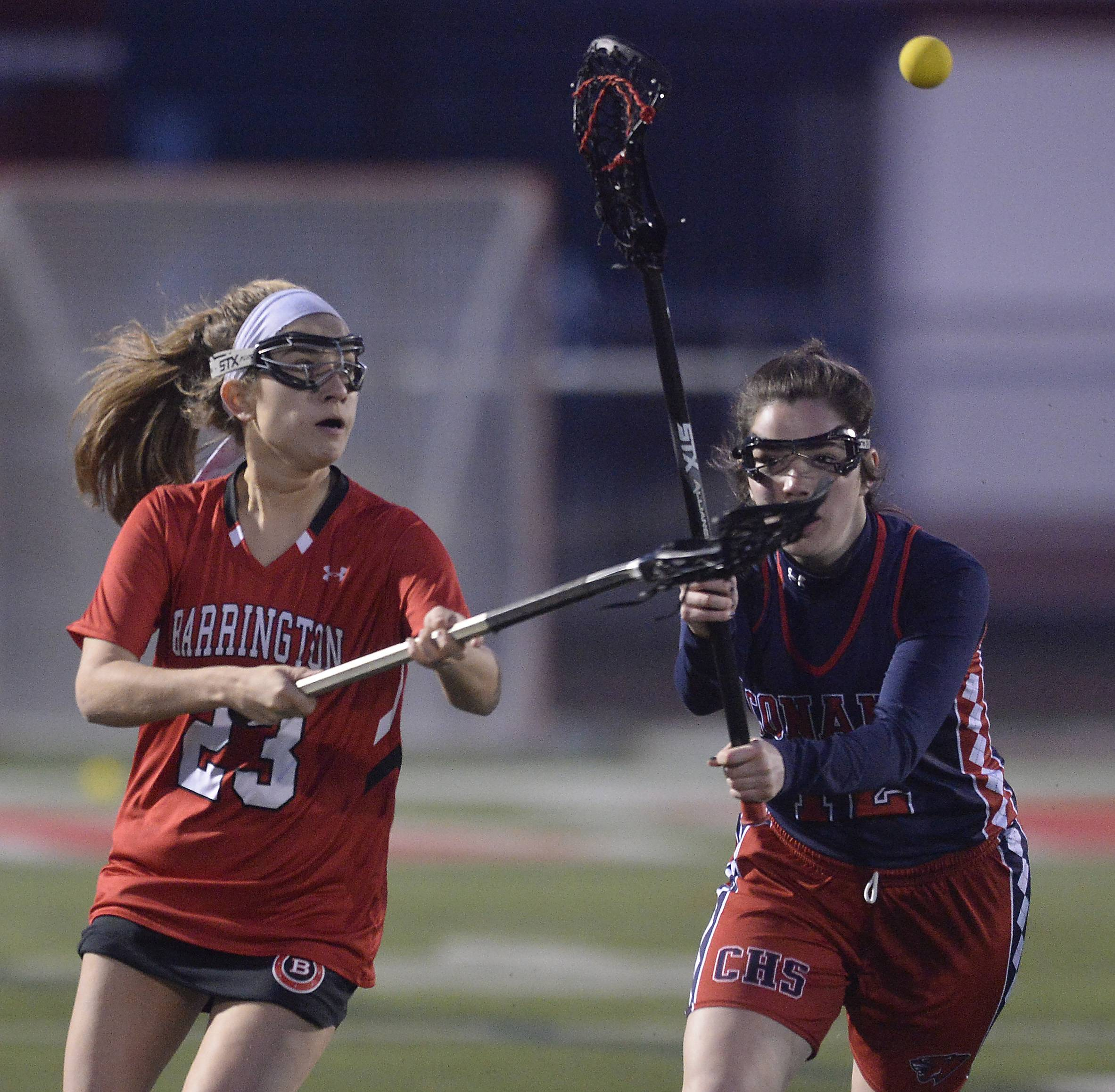 Barrington's Morgan Thorndyke eyes the ball as Conant's Mallory Mills applies defense in girls varsity Lacrosse at Barrington.