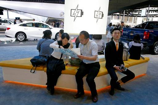 FILE - In this April 19, 2017, file photo, visitors to the stands of GM brands Chevrolet and Buick seat near a section promoting electric power during Auto Shanghai 2017 show at the National Exhibition and Convention Center in Shanghai, China. China has announced plans to allow full foreign ownership of automakers in five years, ending restrictions that have strained relations with Washington and other trading partners.