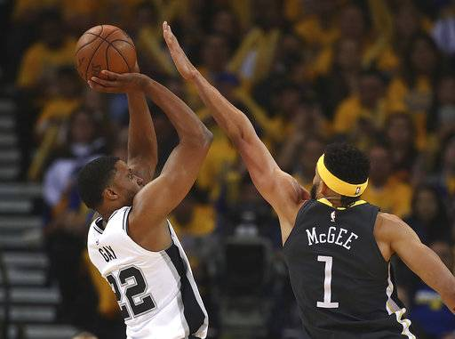 San Antonio Spurs' Rudy Gay, left, shoots against Golden State Warriors' JaVale McGee (1) during the first quarter in Game 2 of a first-round NBA basketball playoff series Monday, April 16, 2018, in Oakland, Calif.
