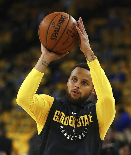 Golden State Warriors' Stephen Curry warms up prior to Game 2 of a first-round NBA basketball playoff series against the the San Antonio Spurs, Monday, April 16, 2018, in Oakland, Calif.