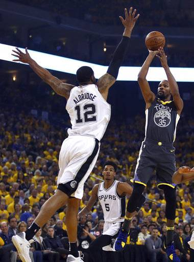 Golden State Warriors' Kevin Durant, right, shoots against San Antonio Spurs' LaMarcus Aldridge (12) during the first quarter in Game 2 of a first-round NBA basketball playoff series Monday, April 16, 2018, in Oakland, Calif.