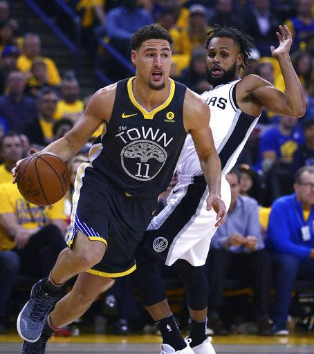Golden State Warriors' Klay Thompson (11) drives the ball away from San Antonio Spurs' Patty Mills, right, during the first quarter in Game 2 of a first-round NBA basketball playoff series Monday, April 16, 2018, in Oakland, Calif.