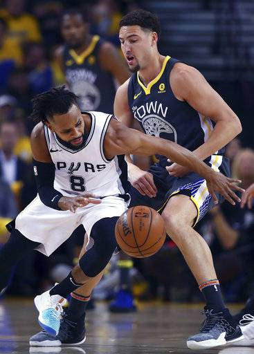 Golden State Warriors' Klay Thompson, right, guards San Antonio Spurs' Patty Mills (8) during the first quarter in Game 2 of a first-round NBA basketball playoff series Monday, April 16, 2018, in Oakland, Calif.