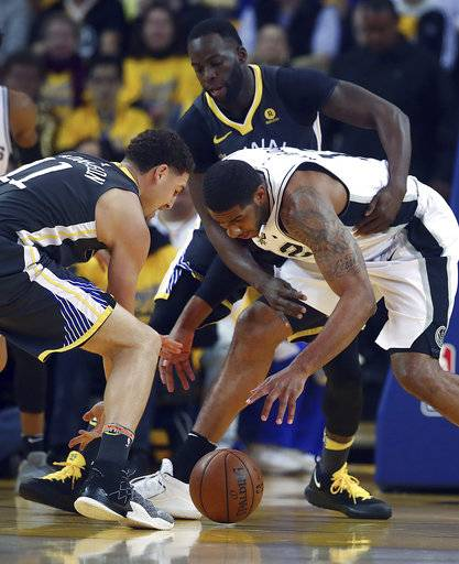 Golden State Warriors' Klay Thompson, left, Draymond Green, center, and San Antonio Spurs' LaMarcus Aldridge (12) fight for a loose ball during the first quarter in Game 2 of a first-round NBA basketball playoff series Monday, April 16, 2018, in Oakland, Calif.
