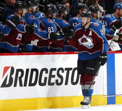 Colorado Avalanche center Nathan MacKinnon, front, is congratulated after scoring a goal against the Nashville Predators as he passes the team box in the second period of Game 3 of an NHL hockey first-round playoff series Monday, April 16, 2018, in Denver.