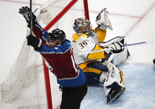 Nashville Predators goaltender Pekka Rinne, back, drops to the ice after missing a shot off the stick of Colorado Avalanche left wing Blake Comeau for a goal in the first period of Game 3 of an NHL hockey first-round playoff series Monday, April 16, 2018, in Denver.