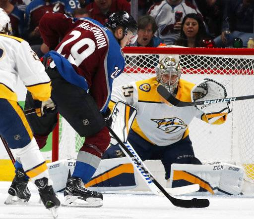 Colorado Avalanche center Nathan MacKinnon, front, fires a shot at Nashville Predators goaltender Pekka Rinne for a goal in the second period of Game 3 of an NHL hockey first-round playoff series Monday, April 16, 2018, in Denver.