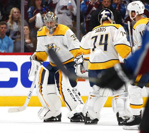 Nashville Predators goaltender Pekka Rinne, left, skates back to the team box as he is replaced by backup goaltender Juuse Saros after giving up a goal to Colorado Avalanche center Nathan MacKinnon in the second period of Game 3 of an NHL hockey first-round playoff series Monday, April 16, 2018, in Denver.