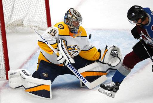 Nashville Predators goaltender Pekka Rinne, left, deflects a shot off the stick of Colorado Avalanche left wing Gabriel Bourque in the first period of Game 3 of an NHL hockey first-round playoff series Monday, April 16, 2018, in Denver.