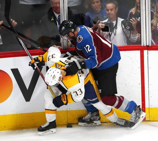 Colorado Avalanche defenseman Patrik Nemeth, hits Nashville Predators left wing Viktor Arvidsson as he tries to control the puck in the first period of Game 3 of an NHL hockey first-round playoff series Monday, April 16, 2018, in Denver.