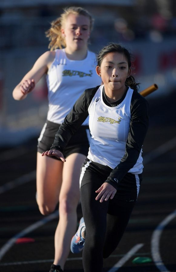 Glenbard North's Delaney Guy reaches for the baton from teammate Alyssa Laherty in the last exchange of the 1,600-meter relay Thursday at the Batavia girls track invitational.