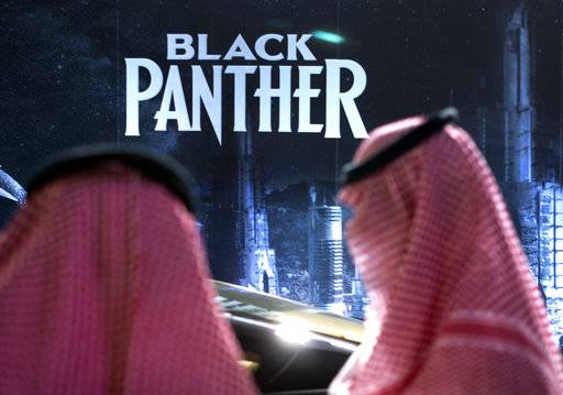 "Visitors wait in front of a ""Black Panther"" movie banner, during an invitation-only screening, at the King Abdullah Financial District Theater, in Riyadh, Saudi Arabia, Wednesday, April 18, 2018. Saudi Arabia held a private screening of the Hollywood blockbuster ""Black Panther"" Wednesday, to herald the launch of movie theaters that are set to open to the public next month."
