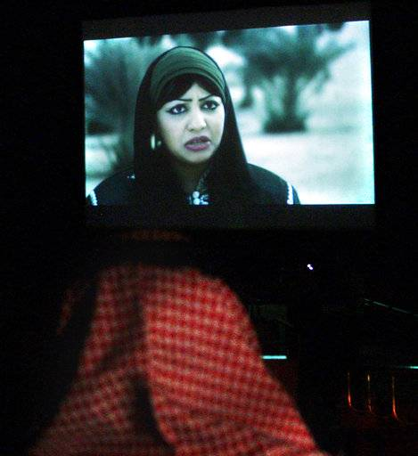 "FILE - In this June 6, 2009 file photo, a Saudi man watches the film, ""Menahi,"" produced by a company owned by Prince Alwaleed bin Talal, at a government-run cultural center, in Riyadh, Saudi Arabia. A private screening Wednesday, April 18, 2018, of the Hollywood blockbuster ""Black Panther"" will herald the launch of movie theaters that are set to open to the public next month. The kingdom's authorities are planning an invitation-only screening of the movie in a concert hall that's been converted into a cinema complex in the capital, Riyadh."