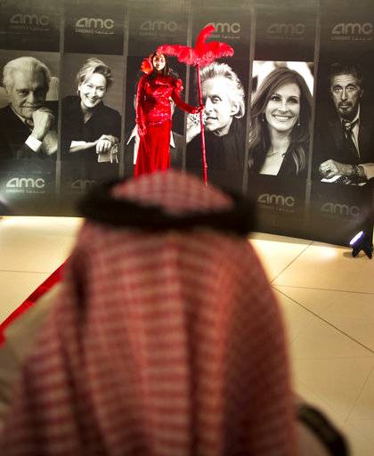 "A visitor takes pictures for an actress with a red dress in front of posters of Hollywood movie stars during invitation-only screening, at the King Abdullah Financial District Theater, in Riyadh, Saudi Arabia, Wednesday, April 18, 2018. Saudi Arabia held a private screening of the Hollywood blockbuster ""Black Panther"" Wednesday, to herald the launch of movie theaters that are set to open to the public next month."