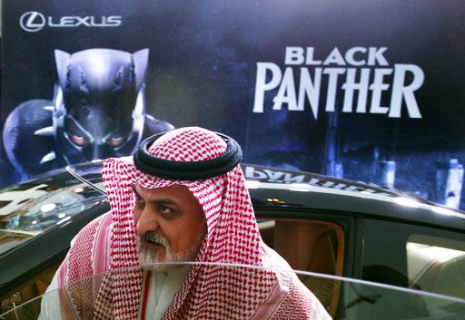 "A visitor checks out a Lexus car, similar to a one used in the Black Panther film, that is on display outside an invitation-only screening, at the King Abdullah Financial District Theater, in Riyadh, Saudi Arabia, Wednesday, April 18, 2018. Saudi Arabia held a private screening of the Hollywood blockbuster ""Black Panther""  Wednesday, to herald the launch of movie theaters that are set to open to the public next month."