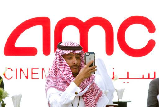 "A visitor takes a selfie with a screen displaying the announcement of the first cinema, at the King Abdullah Financial District Theater, in Riyadh, Saudi Arabia, Wednesday, April 18, 2018. Saudi Arabia will hold a private screening of the Hollywood blockbuster ""Black Panther"" to herald the launch of movie theaters that are set to open to the public next month."