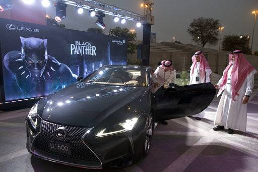 "A visitor checks out a Lexus car, similar to a one used in the film ""Black Panther,""  that is on display outside an invitation-only screening, at the King Abdullah Financial District Theater, in Riyadh, Saudi Arabia, Wednesday, April 18, 2018. Saudi Arabia will hold a private screening of the Hollywood blockbuster ""Black Panther""  Wednesday, to herald the launch of movie theaters that are set to open to the public next month."