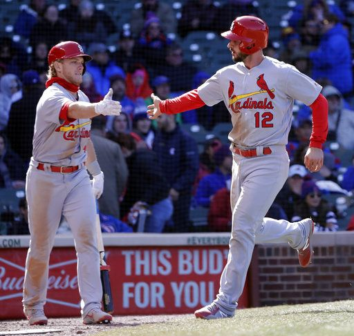 St. Louis Cardinals' Harrison Bader, left, greets Paul DeJong (12) outside the dugout after DeJong scored on a ball hit by Dexter Fowler during the seventh inning of a baseball game against the Chicago Cubs, Thursday, April 19, 2018, in Chicago.