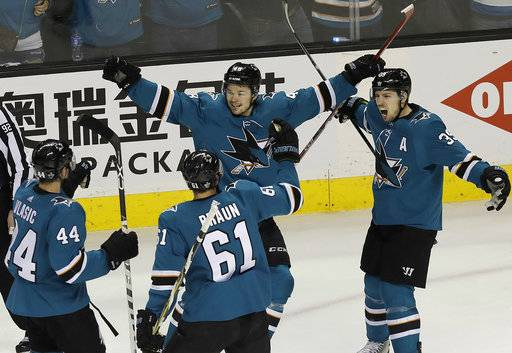 San Jose Sharks center Tomas Hertl, center, from the Czech Republic, celebrates with Marc-Edouard Vlasic (44), Justin Braun (61) and Logan Couture after scoring a goal against the Anaheim Ducks during the third period of Game 4 of an NHL hockey first-round playoff series in San Jose, Calif., Wednesday, April 18, 2018. The Sharks won 2-1 to sweep the series.