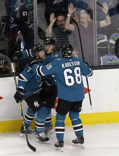 San Jose Sharks left wing Marcus Sorensen, center, is congratulated by defenseman Paul Martin (7) and right wing Melker Karlsson (68), from Sweden, after scoring a goal against the Anaheim Ducks during the first period of Game 4 of an NHL hockey first-round playoff series in San Jose, Calif., Wednesday, April 18, 2018.