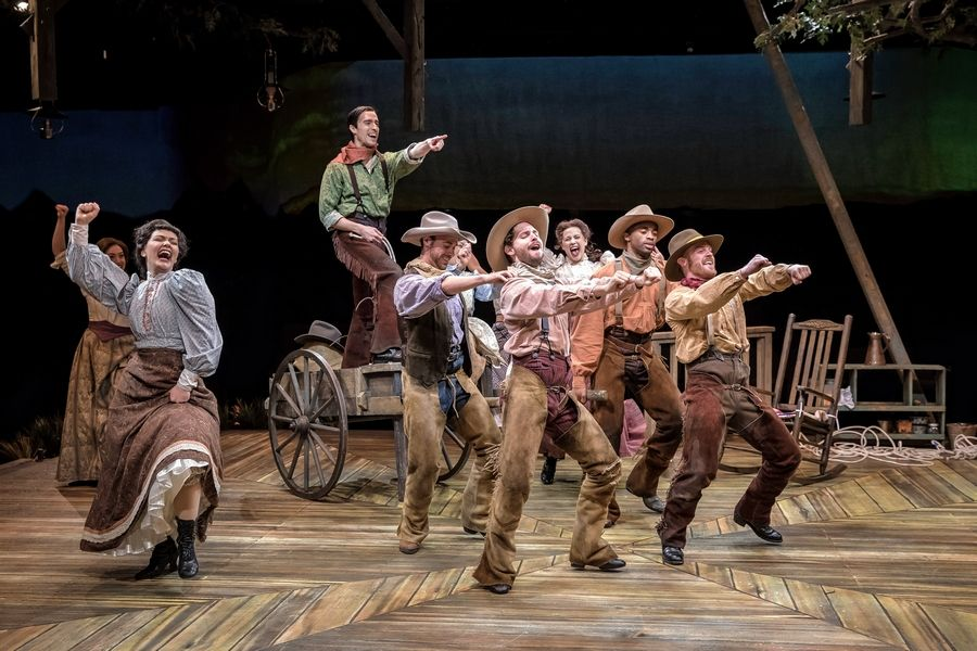 "Will Parker (Aaron Umsted), atop wagon, gets the ensemble worked up over how everything is up to date in ""Kansas City"" in ""Oklahoma!"" at the Marriott Theatre in Lincolnshire."