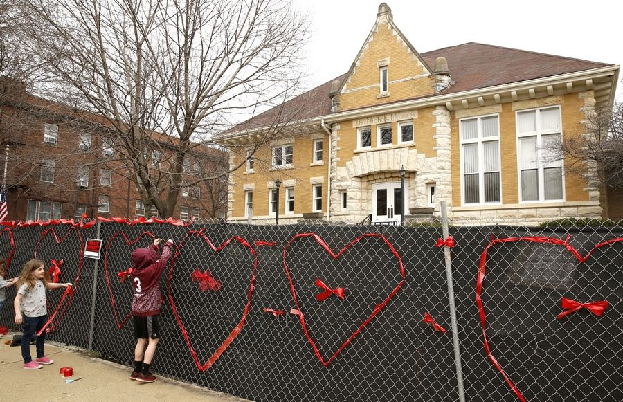 Norra Brown, left, and her brother Reid, right, assist members of the Save Old Nichols group who spent part of Saturday afternoon decorating the construction fencing around the property with a heart made of ribbons so passers-by know that, even as the library is being demolished, there are those in town who love it.