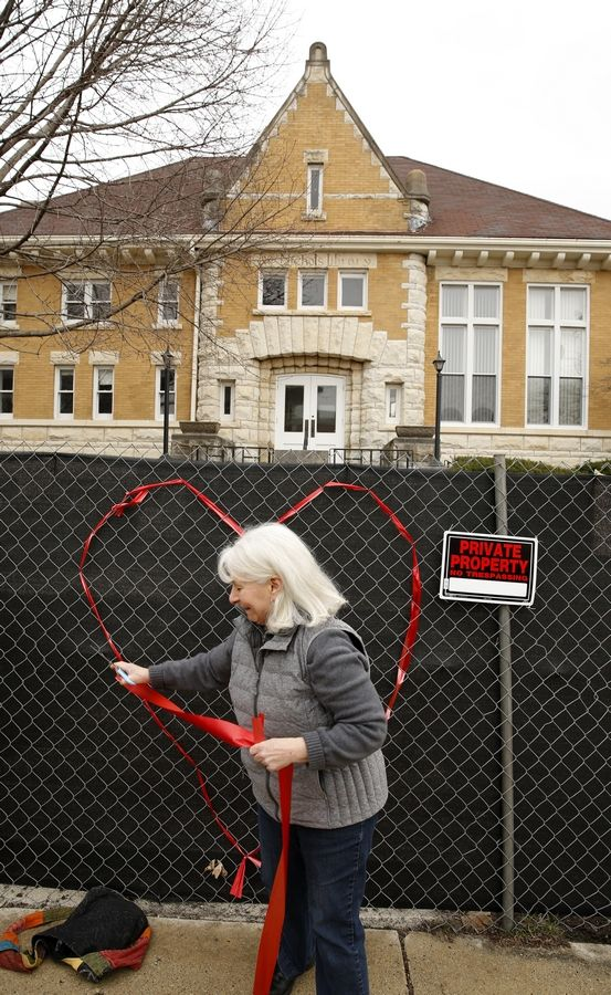 Gail Diedrichsen of Naperville was one of about a dozen members of the Save Old Nichols group who decorated the construction fencing around the downtown Naperville property with a heart made of ribbons how much it means to them.