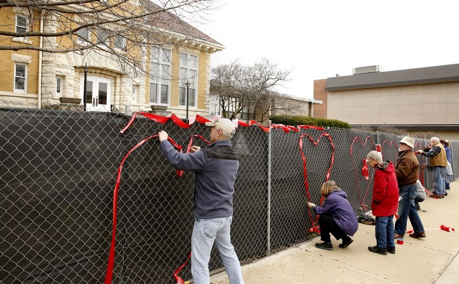 Bill Simon, left, of Naperville helped the Save Old Nichols group decorate the construction fencing around the property with a heart made of ribbons so passers-by know that, even as the former Naperville library is being demolished, there are those in town who love it.