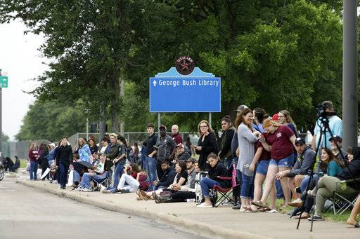 People line up to pay tribute as they wait for the motorcade carrying former first lady Barbara Bush on George Bush Drive, Saturday, April 21, 2018, in College Station, Texas.