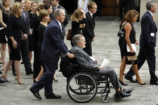 Former President George W. Bush pushes his father, former President George H.W. Bush to a motorcade after a funeral service for former first lady Barbara Bush at St. Martin's Episcopal Church, Saturday, April 21, 2018, in Houston.