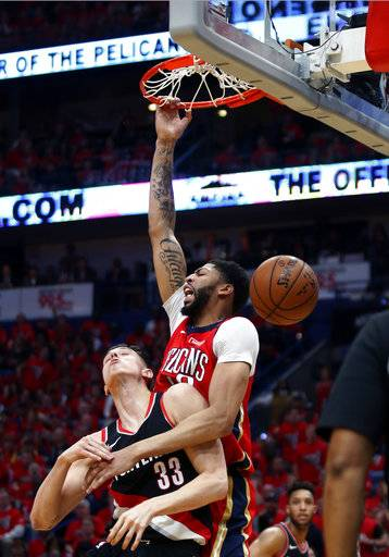 New Orleans Pelicans forward Anthony Davis, top, slam-dunks over Portland Trail Blazers center Zach Collins (33) during the first half of Game 4 of a first-round NBA basketball playoff series in New Orleans, Saturday, April 21, 2018.