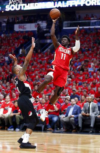 New Orleans Pelicans guard Jrue Holiday (11) shoots over Portland Trail Blazers guard Damian Lillard (0) during the first half of Game 4 of a first-round NBA basketball playoff series in New Orleans, Saturday, April 21, 2018.