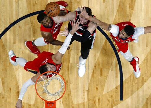 Portland Trail Blazers center Jusuf Nurkic shoots under pressure form New Orleans Pelicans' Anthony Davis, right, guard Ian Clark, top left, and Nikola Mirotic, bottom left, during the first half of Game 4 of a first-round NBA basketball playoff series in New Orleans, Saturday, April 21, 2018.