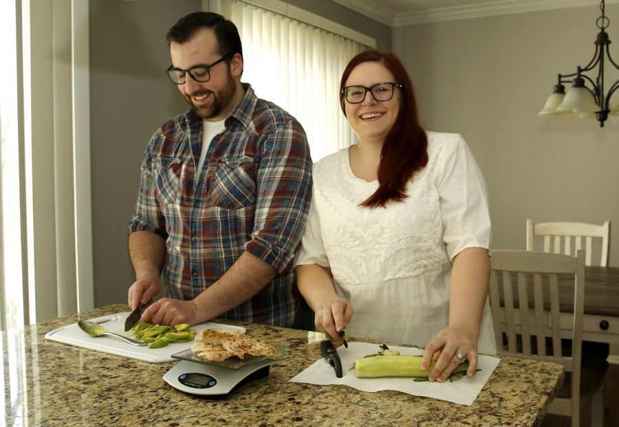 Kim Rosewell gets some help from her fiance, Kyle Spires of Roselle, to prepare healthy lunches, which partially consist of baked chicken breasts, cucumbers and avocados.