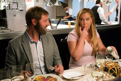 "This image released by STX Films shows Rory Scovel, left, and Amy Schumer in a scene from ""I Feel Pretty."" (Mark Schafer/STX via AP)"