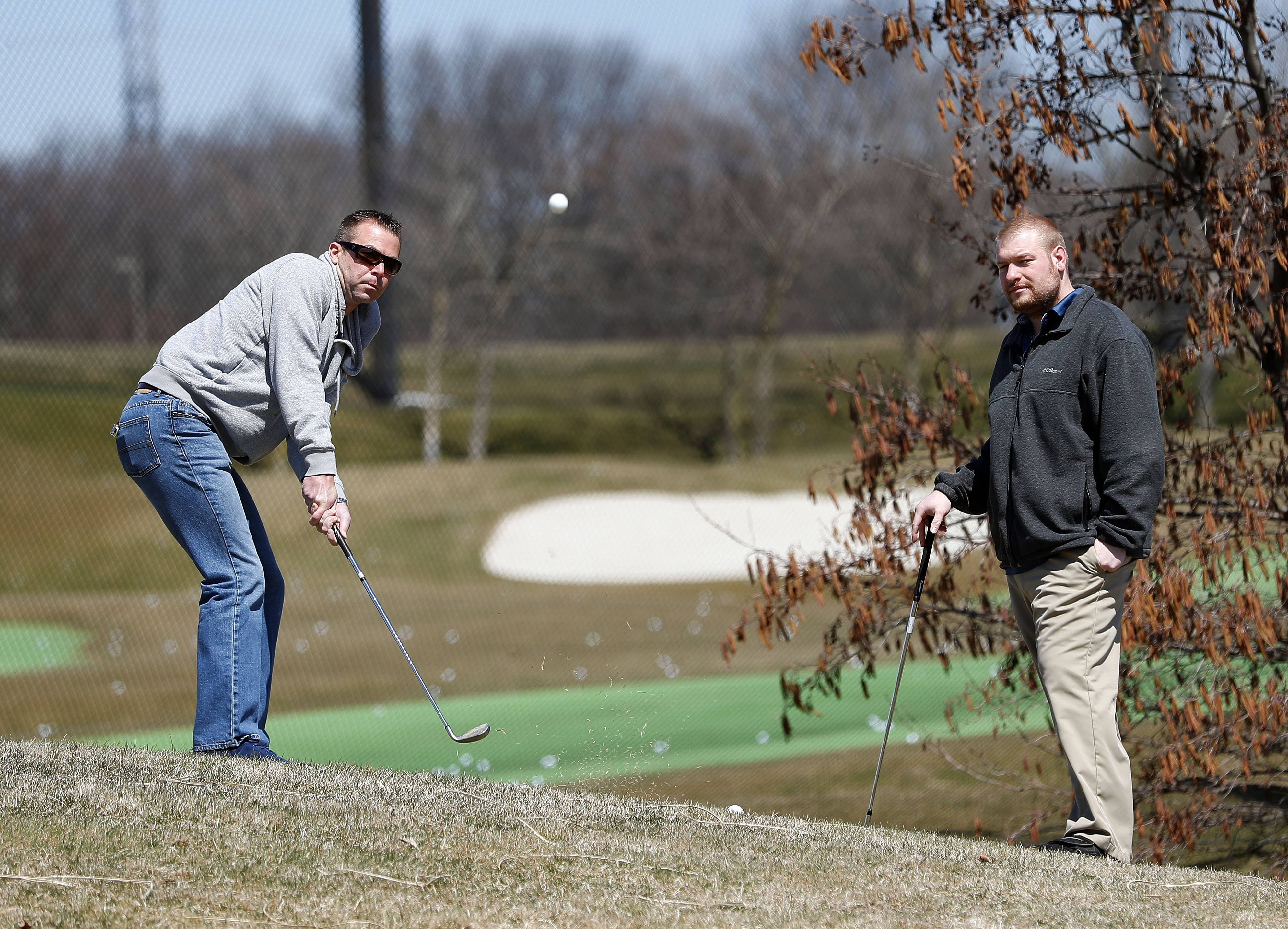 Jon Merrick of Chicago, left, and Cory Gaul of Wauconda take advantage of temperatures in the 50s to practice their chipping Thursday at Libertyville Sports Complex.