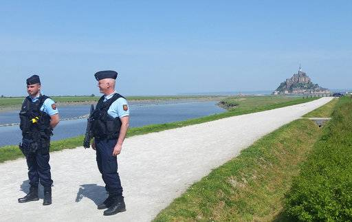 Police attend the scene of an evacuation at Mont Saint-Michel, on France's northern coast, Sunday April 22, 2018. Authorities are evacuating tourists and others from the Mont-Saint-Michel abbey and monument in western France after a visitor apparently threatened to attack security services.