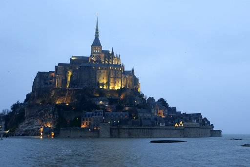 FILE - In this Friday, March 20, 2015 file photo, the Mont Saint-Michel pictured by night, in western France. Authorities are evacuating tourists and others from the Mont-Saint-Michel abbey and monument in western France on Sunday April 22, 2018, after a visitor apparently threatened to attack security services.