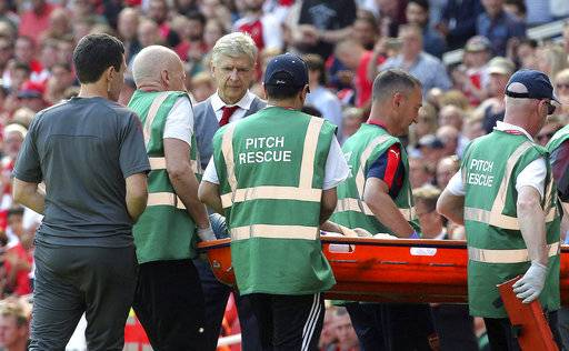 Arsenal's Arsene Wenger watches as Mohamed Elneny leaves the pitch injured on a stretcher during the English Premier League soccer match against West Ham United at the Emirates Stadium, London, Sunday April 22, 2018. (Mark Kerton/PA via AP)