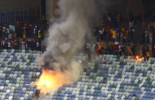 A fire burns in the stands at the Moses Mabhida stedium in Durban, South Africa, Saturday, April 21, 2018, after violence broke out at a soccer game when hundreds of fans ripped up parts of the stadium, invaded the pitch, and assaulted at least one security guard. The incident occurred after the Kaizer Chiefs lost 2-0 to Free State Stars in the semifinals of the Nedbank Cup competition.